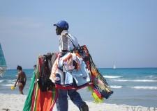Rimini. Legalità. Cliente sanzionata in spiaggia dopo aver acquistato una borsa contraffatta da un venditore abusivo.